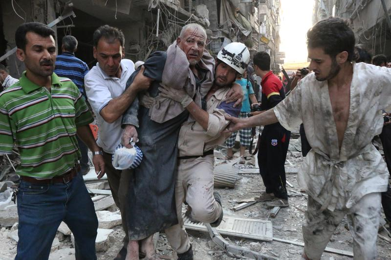 A rescue worker and residents carry an injured man following a reported air strike by Syrian government forces on July 27, 2014 in the northern city of Aleppo.