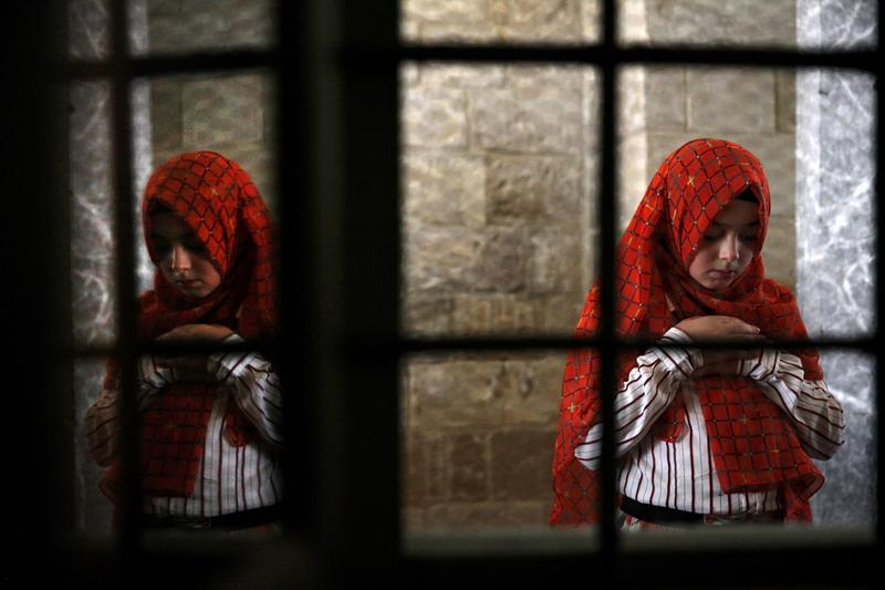 A Muslim girl prays inside Hala Sultan Tekke mosque in the coastal Cypriot city of Larnaca on July 28, 2014 on the first day of Eid al-Fitr, that marks the end of the fasting month of Ramadan.