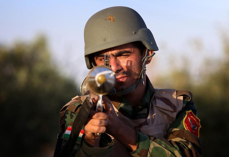 An Iraqi Kurdish Peshmerga fighter poses for a picture on the front line in Makhmur, about 175 miles north of the capital Baghdad, during clashes with Islamic State (IS) militants. August 9, 2014