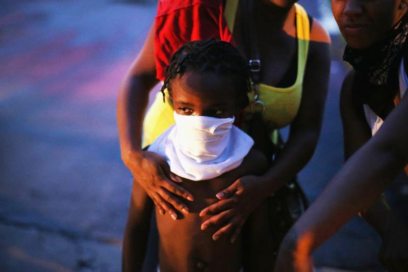 A child uses a rag to shield his face from tear gas being fired by police who used it to force protestors from the business district into nearby neighborhoods on August 11, 2014 in Ferguson, Missouri.