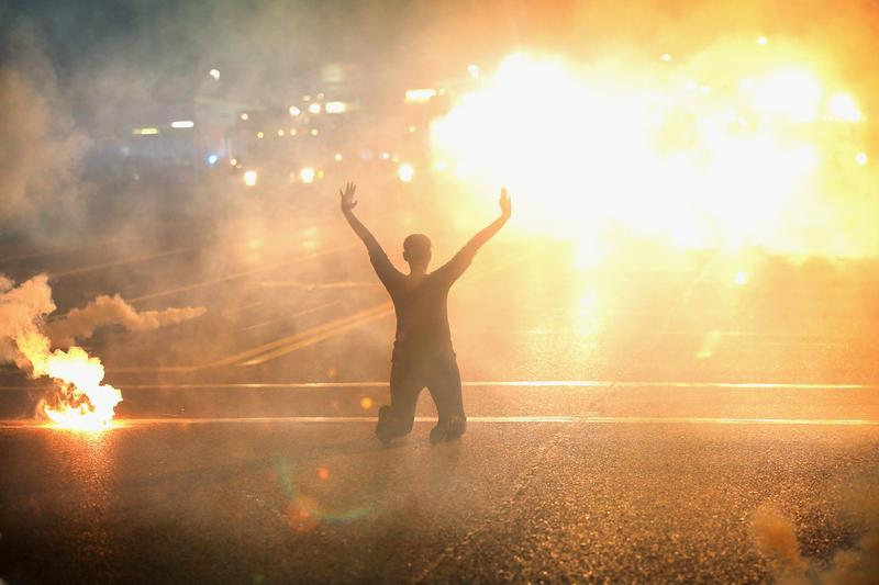 Tear gas reigns down on a woman kneeling in the street with her hands in the air after a demonstration over the killing of teenager Michael Brown by a Ferguson police officer on August 17, 2014.