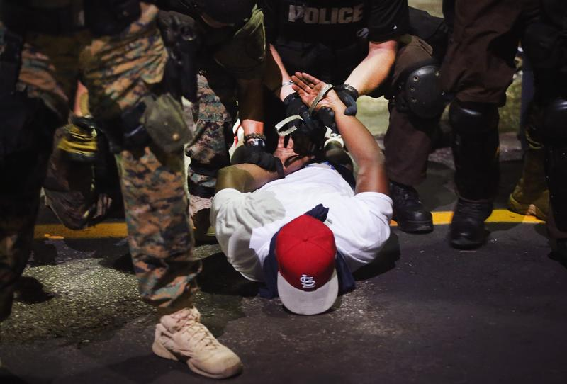 Police arrest a demonstrator protesting the killing of teenager Michael Brown on August 19, 2014 in Ferguson, Missouri.