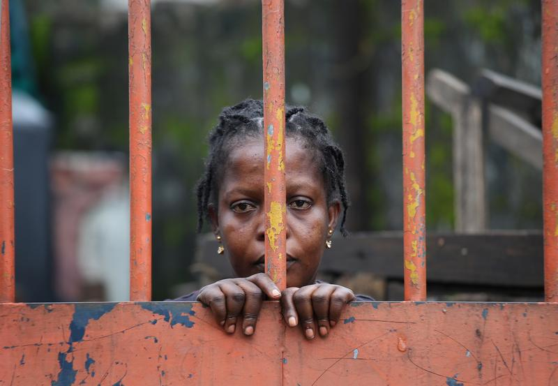 A West Point slum resident looks from behind closed gates on the second day of the government's Ebola quarantine on their neighborhood on August 21, 2014 in Monrovia, Liberia.