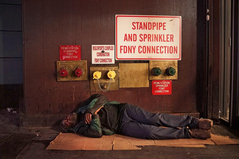 A homeless man sleeps on a Manhattan street.
