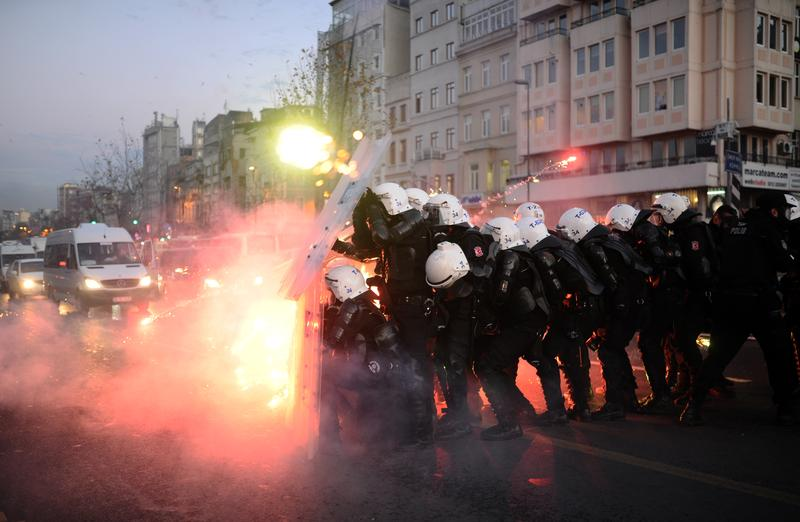 Turkish riot police officers take cover as Kurdish protesters shoot fireworks at them during clashes in central Istanbul on December 7, 2013.