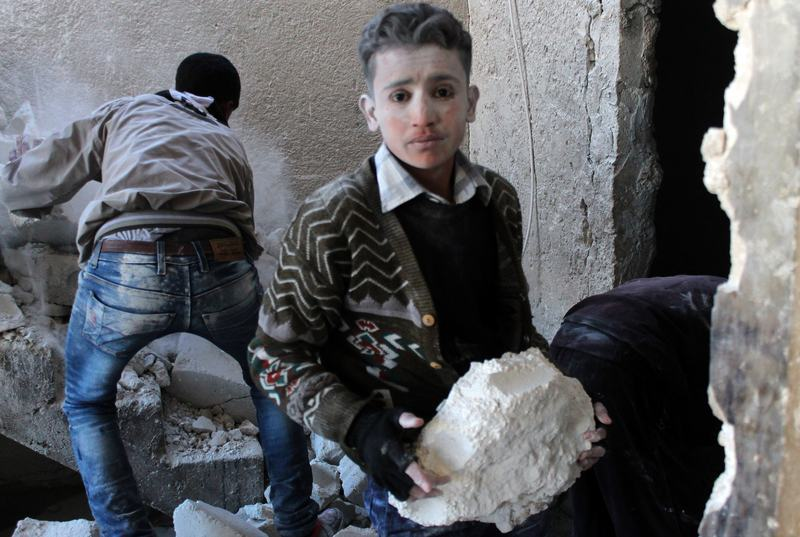 A young Syrian, covered is dust, helps clear the debris after the Syrian airforce allegedly fired at a residential neighborhood. December 9, 2013