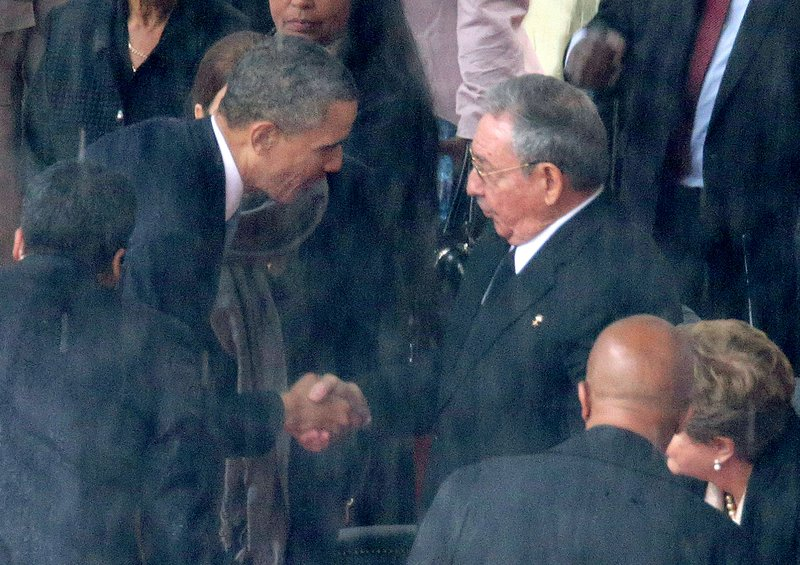 U.S. President Barack Obama (L) shakes hands with Cuban President Raul Castro during the official memorial service for former South African President Nelson Mandela at FNB Stadium December 10, 2013.