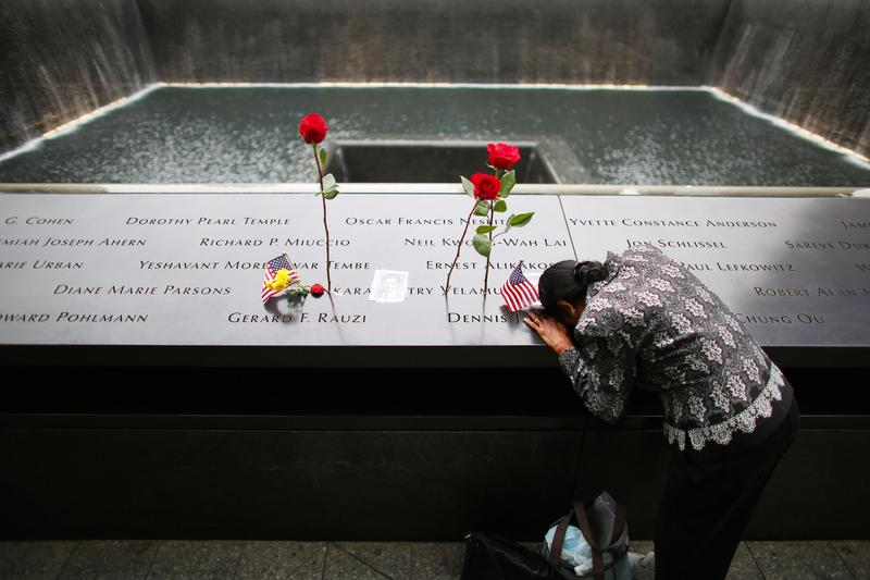 A woman grieves at her husband's memorial at South Tower Reflecting Pool before the memorial observances held at the site of the World Trade Center. Sept. 11, 2014