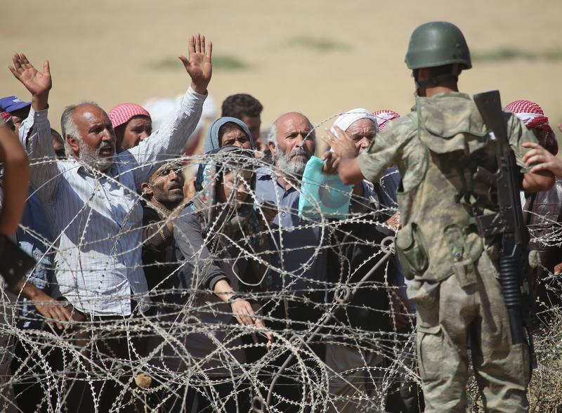 Syrians fleeing from clashes between ISIS militants and Democratic Union Party (PYD) forces in the Ar-Raqqah Governorate of Syria, wait at the Turkish-Syrian border. Sept. 19, 2014