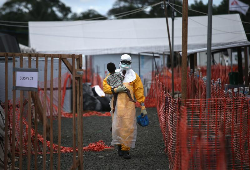 A Doctors Without Borders (MSF), health worker in protective clothing carries a child suspected of having Ebola in the MSF treatment center on October 5, 2014 in Paynesville, Liberia.