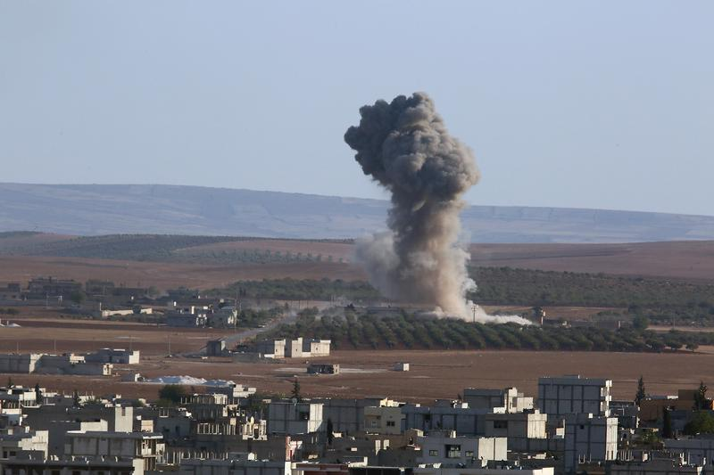 A photograph taken from Sanliurfa, Turkey, shows that smoke rises from the Syrian city of Kobani after the U.S.-led coalition bombed ISIS targets. Oct. 7, 2014