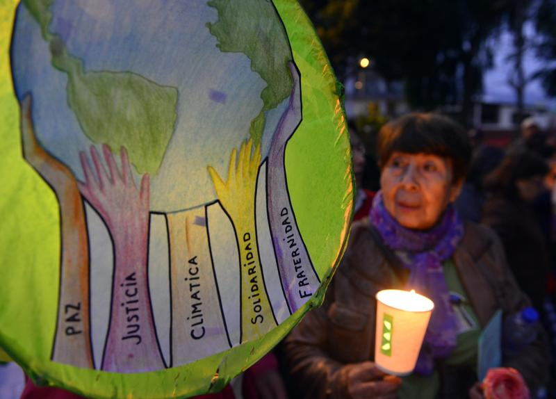 People attend a candlelight vigil organized by the Interfaith Council of Peru at a park in Lima, on Nov. 30, 2014, just hours before the opening of Climate Change Conference hosted by the government.