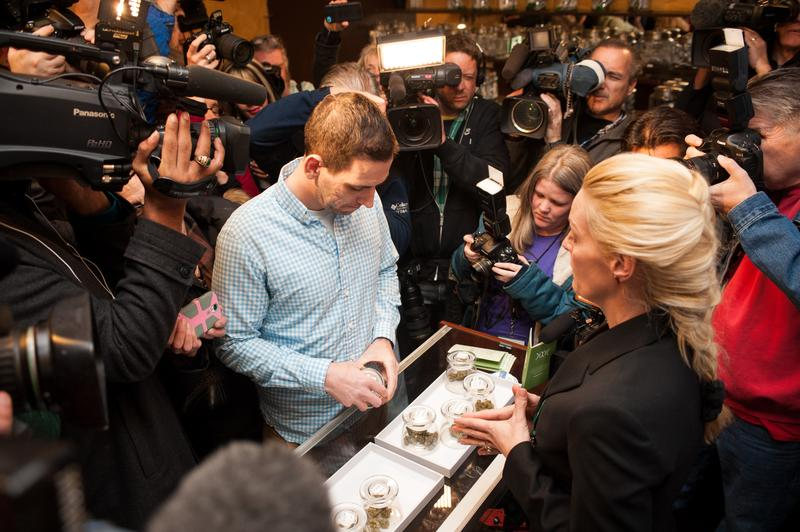 Sean Azzariti, a veteran of the Iraq war, prepares to make the first legal recreational marijuana purchase in Colorado from advocate Betty Aldworth at the 3-D Denver Discrete Dispensary on January 1.