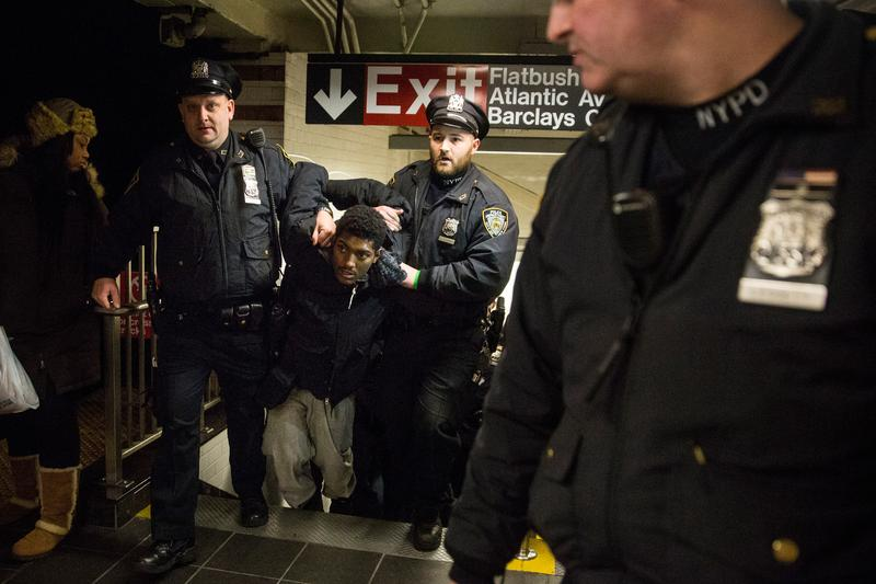 Police arrest a demonstrator protesting the grand jury's decision not to indict a police officer involved in the chokehold death of Eric Garner inside the Barclays Center subway station. Dec. 8, 2014