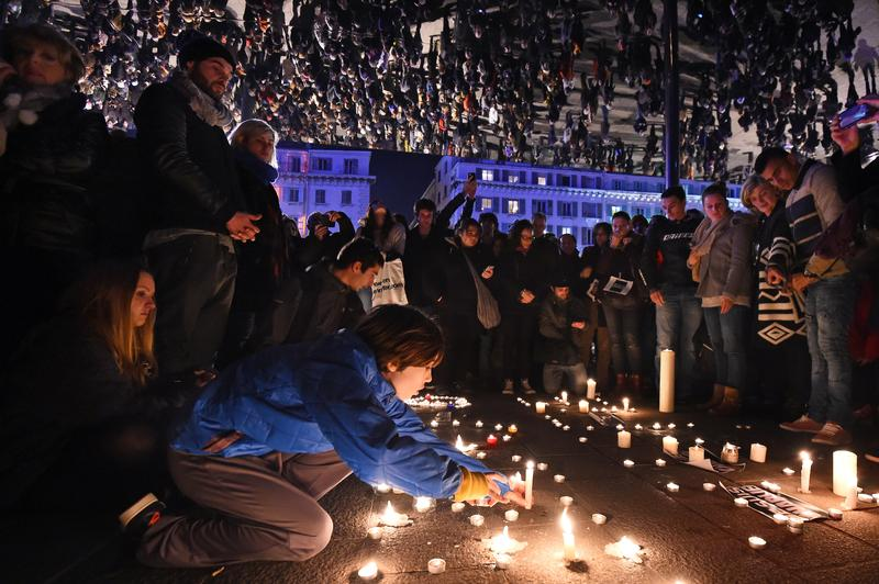People gather to light candles under large mirror panels on the Old Port of Marseille, southern France, on January 7, 2015, following an attack Charlie Hebdo.
