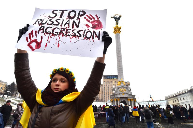 A girl wearing Ukrainian flag holds placard reading 'Stop Russian aggression' at Independence Square in Kiev on Jan. 25, 2015, during a rally for people who died as a result of shelling in Mariupol.