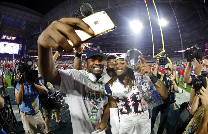 Members of the New England Patriots celebrate with the Vince Lombardi Trophy after defeating the Seattle Seahawks 28-24 in Super Bowl XLIX.