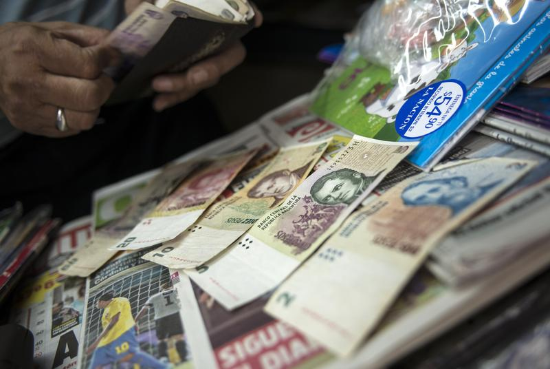 Newsstand owner counts Argentine pesos, 01/24/14. Argentina lifted financial restrictions in place since 2011, a day after the peso suffered its worst single-day dive since the 2002 financial crisis.