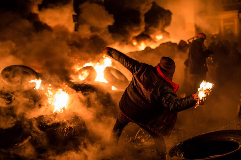 An anti-government protester throws a Molotov cocktail during clashes with police on Hrushevskoho Street near Dynamo stadium on January 25, 2014 in Kiev, Ukraine.