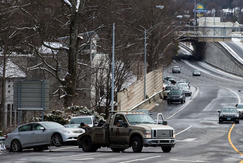 A tow truck pulls an abandoned vehicle on an exit ramp along I-75 North during the winter storm January 29, 2014 in Atlanta, Georgia