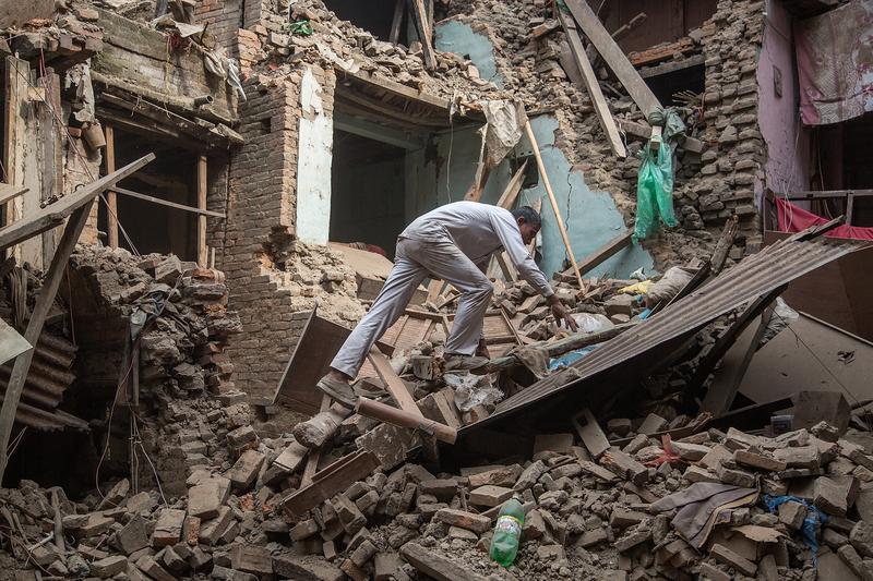A man climbs on top of debris after buildings collapsed on April 26, 2015 in Bhaktapur, Nepal, after a major 7.8 earthquake hit Kathmandu mid-day on Saturday.