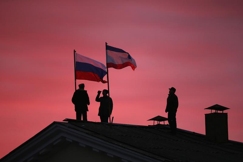 Cossack men install a Russian flag and a Crimean flag on the roof of the City Hall building on March 17, 2014 in Bakhchysarai, Ukraine.