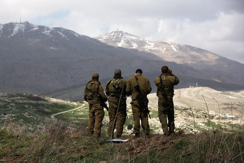Israeli soldiers deployed on the border with Syria observe Syrian territory from Israeli side of the border on March 19, 2014 in the Israeli-annexed Golan Heights.