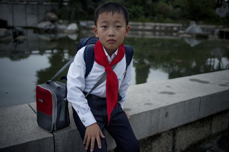 A North Korean schoolboy of Pyongyang sits on the edge of a water pond. Sept. 17, 2013