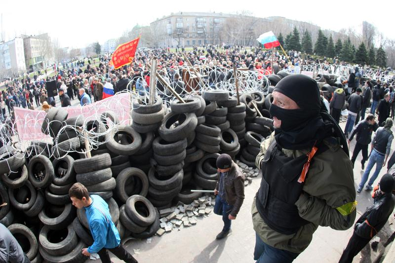 Pro-Russian activists guard a barricade set at the Donetsk regional council office building on the eastern city of Donetsk on April 7, 2014.