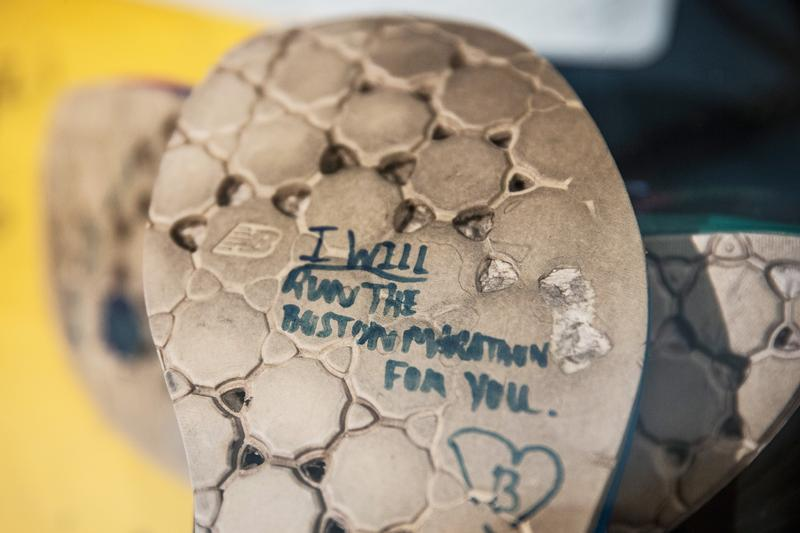 A runner's shoes read, 'I will run the Boston Marathong for you,' in a display titled, 'Dear Boston: Messages from the Marathon Memorial' in the Boston Public Library.  April 14, 2014