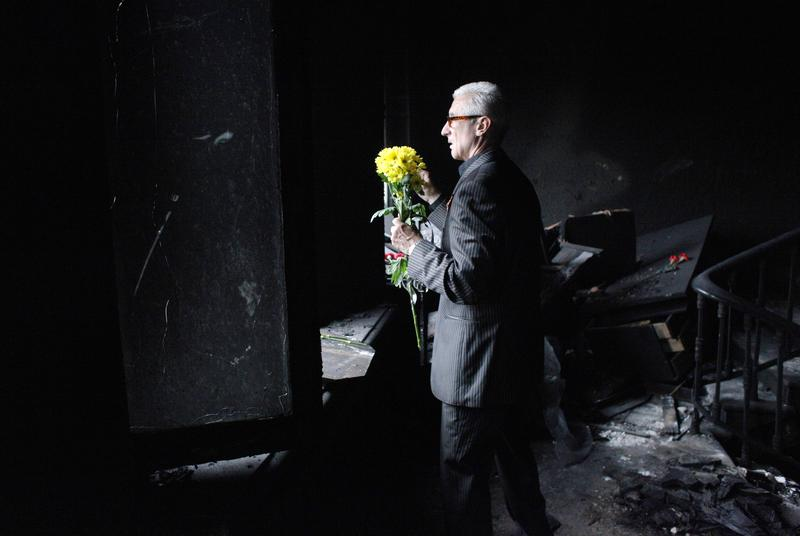 A man holds flowers he brough in homage of the victims as he stands inside the burned trade union building in the southern Ukranian city of Odessa on May 4, 2014.