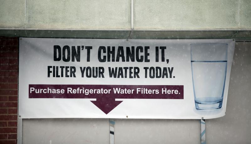 A sign on a the front of a building warns residents to filter their water January 17, 2016 in Flint, Michigan. U.S. President Barack Obama declared a federal emergency in Michigan.