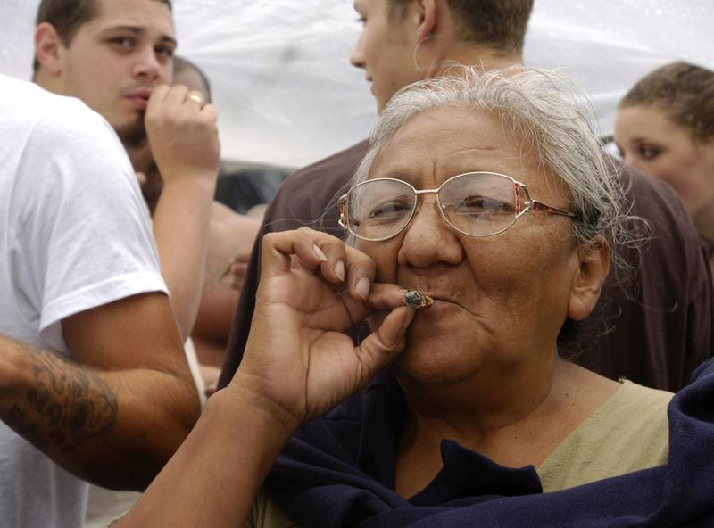 An older woman smokes a marijuana joint at Hempfest on August 21, 2004 in Seattle, Washington.
