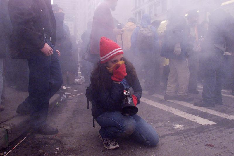 A demonstrator covers her mouth to protect herself from tear gas following street clashes with riot police in downtown Seattle, Washington on the opening day of the WTO meeting. Nov. 30, 1999