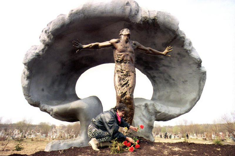 A woman puts flowers at the new memorial to victims of the 1986 Chernobyl nuclear power plant explosion at Mitino cemetery 27 April 1993.