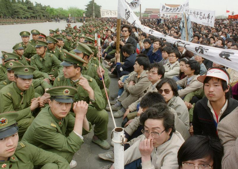 200,000 pro-democracy student protesters face to face with policemen outside the Great Hall of the People in Tiananmen Square 22 April 1989 in Beijing.