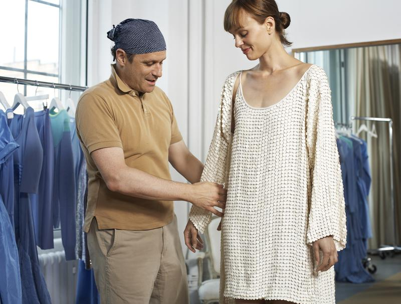 Isaac Mizrahi dressing a model in one of his designs.