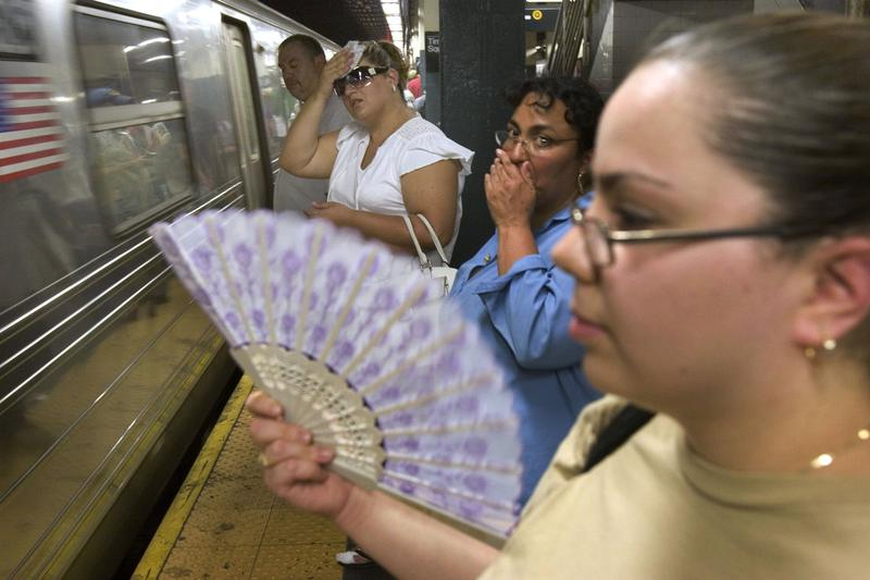 Elena Kobzarenko of Brooklyn fans herself while waiting for a subway, with temperatures hitting the upper 90s.