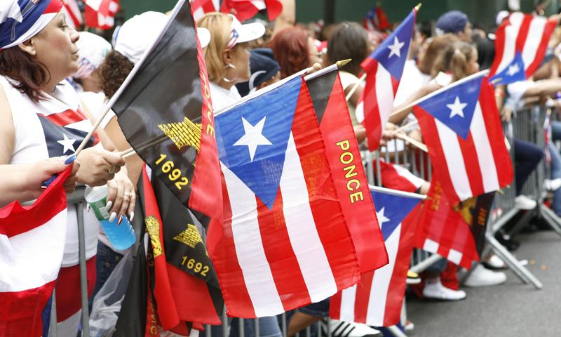 People wave flags during the National Puerto Rican Day Parade in New York City.