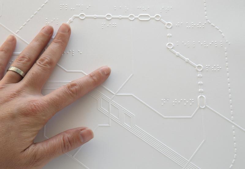 A person touches a braille map of the Parisian metro