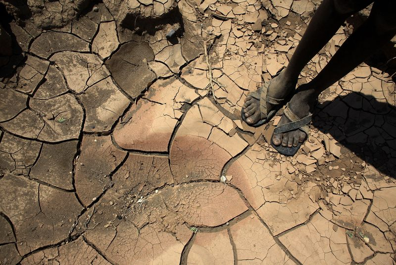 A young boy from the remote Turkana tribe in Northern Kenya stands on a dried up river bed on November 9, 2009. Their way of life is threatened by climate change.