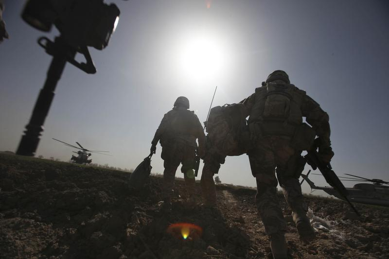 US Marines with NATO forces rush towards a helicopter in Marjah on February 17, 2010.