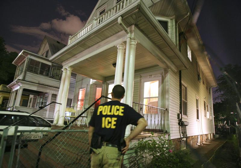 An agent from the Immigration and Customs Enforcement agency keeps watch at the side of a house while other agents from ICE are inside in search of a suspect. June 13, 2006