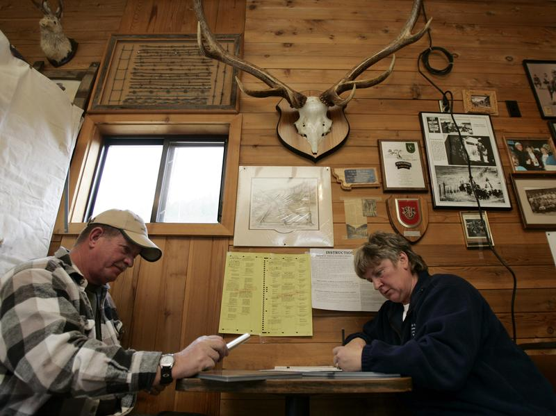 Under mounted antlers and historical photos, Steve and Janet Hren go over their ballots as they vote at the Lazy Doe Saloon in Monarch, Mont., Tuesday, Nov. 7, 2006.