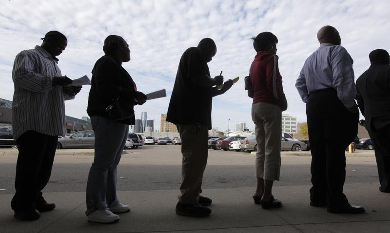 Job seekers fill out applications for positions at a new bar and restaurant while standing in line in Detroit, Sept. 25, 2009.