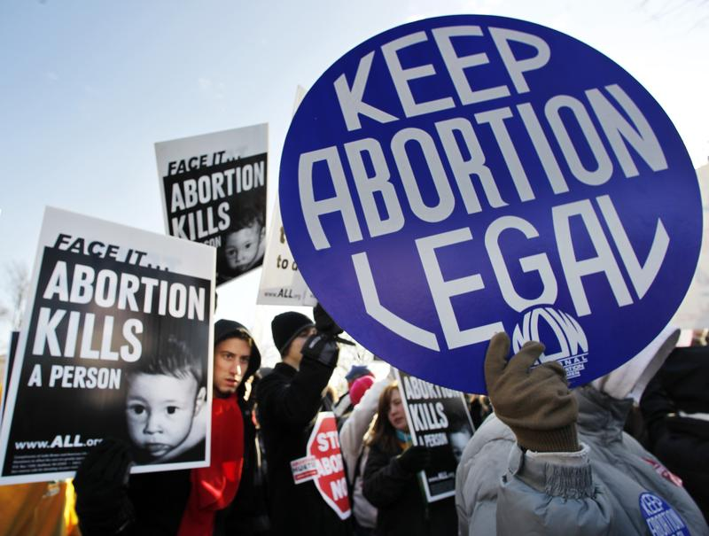 In this Monday, Jan. 24, 2011 file picture, anti-abortion and pro-choice activists stand next to each other in front of the U.S. Supreme Court in Washington.