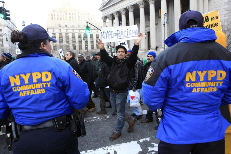 Mariano Munoz, carries a sign past NYPD community affairs officers during rally asking for resignation of NYPD Commissioner R. Kelly & NYPD spokesperson P. Browne, demanding community control of NYPD.