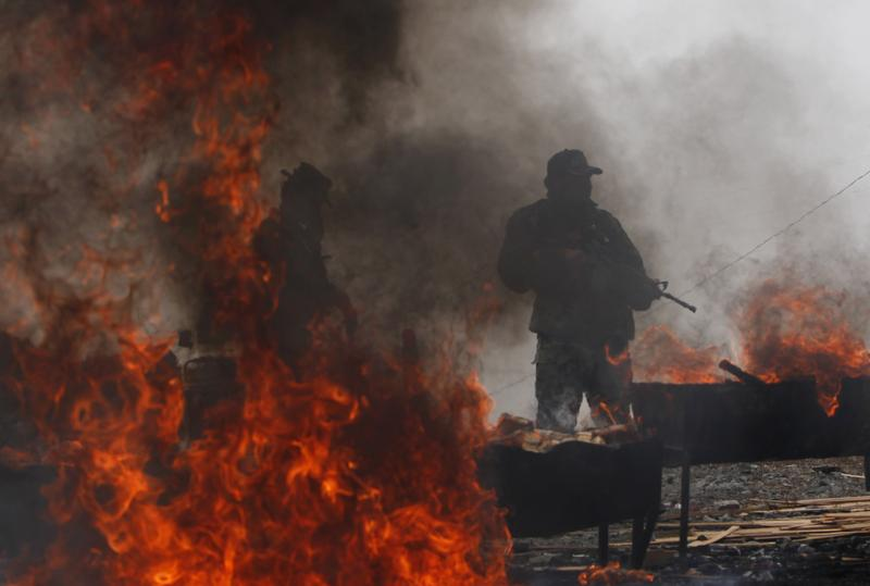 Anti-narcotics police agents stands guard during the incineration of seized cocaine in La Rinconada on the outskirts of La Paz, Bolivia, Tuesday, April 24, 2012.