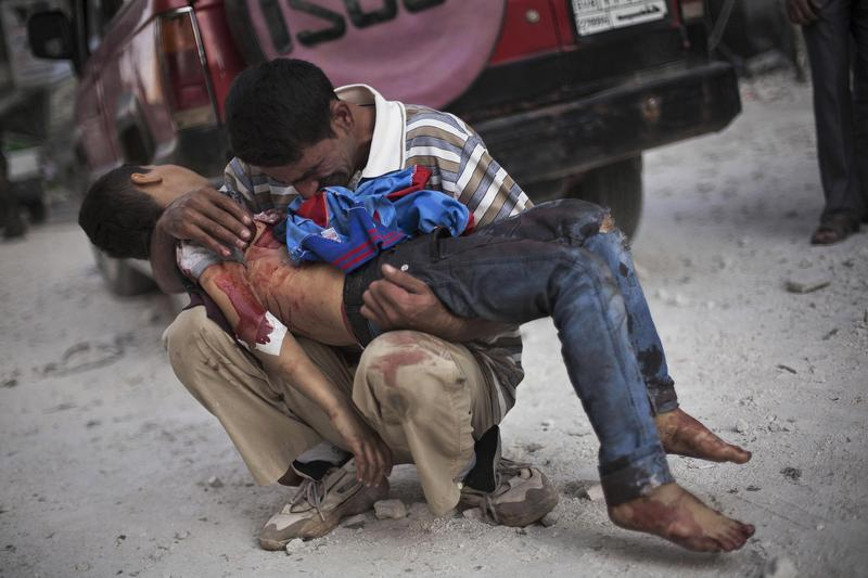 A Syrian man cries while holding the body of his son near Dar El Shifa hospital in Aleppo, Syria, Oct. 3, 2012.