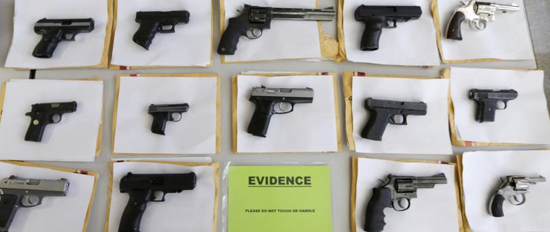 Chicago police display some of the thousands of illegal firearms they confiscated in 2014 as they battle gun violence in Chicago.